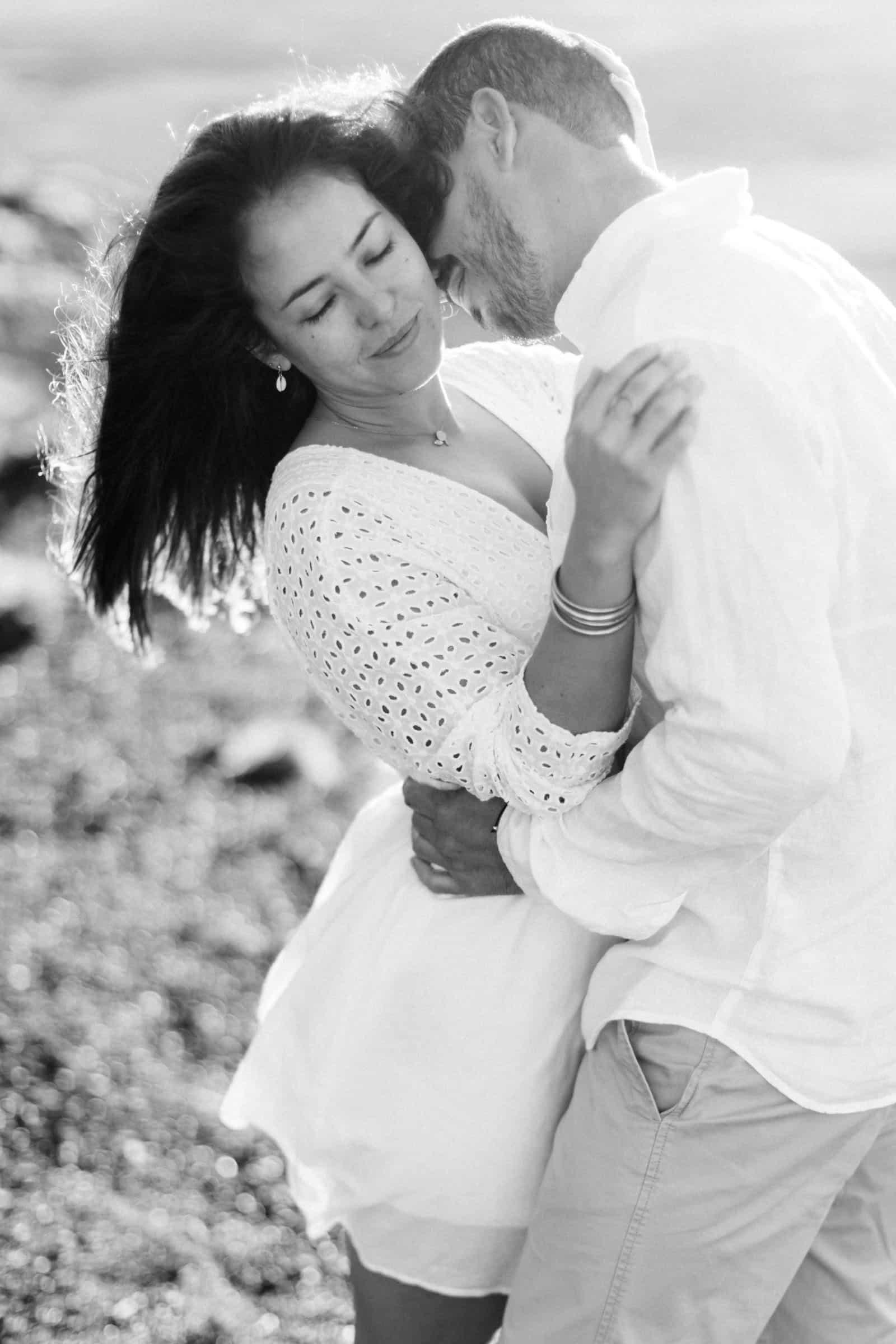 Photographie en noir et blanc de Mathieu Dété, photographe de mariage et famille à Saint-Benoît de la Réunion 974, présentant un couple enlacé au lever du soleil