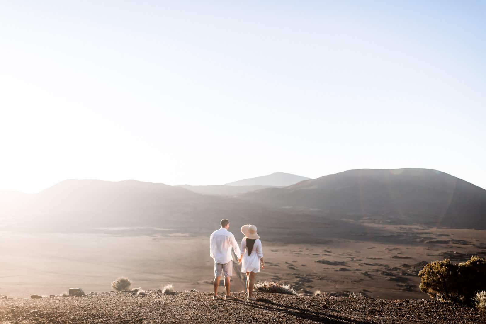 Photographie de Mathieu Dété, photographe de mariage et famille à Saint-Gilles sur l'île de la Réunion 974, présentant un couple qui se tient par la main et qui regarde la route du volcan, le Piton de la Fournaise et la Plaine des Sables