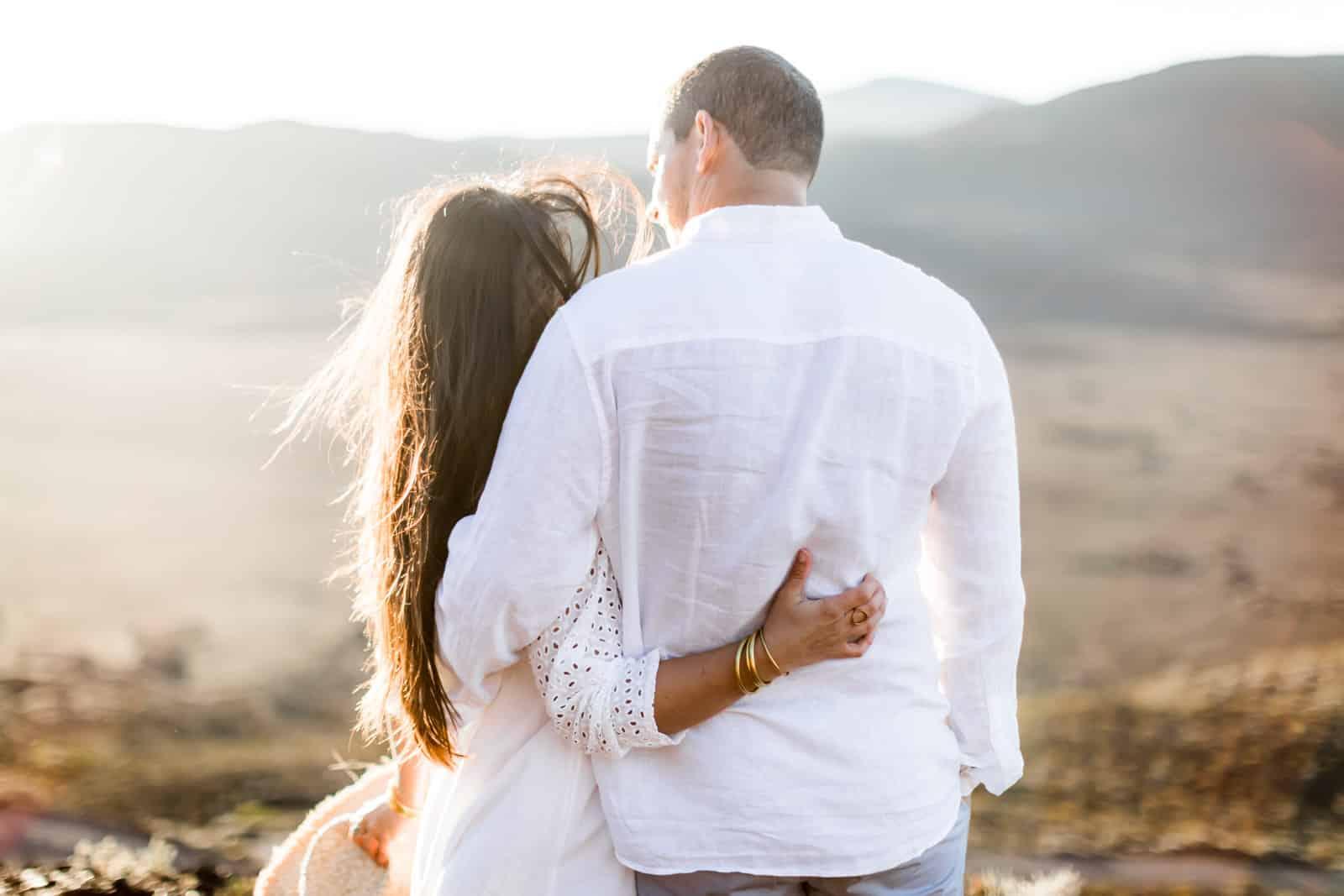 Photographie de Mathieu Dété, photographe de mariage et famille à Saint-Gilles sur l'île de la Réunion 974, présentant un couple enlacé par la taille au lever du soleil en contre-jour durant une séance couple