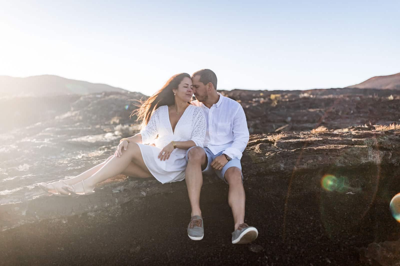 Photographie de Mathieu Dété, photographe de mariage et famille à Saint-Gilles sur l'île de la Réunion 974, présentant un couple assis côte à côte sur une roche de la Plaine des Sables