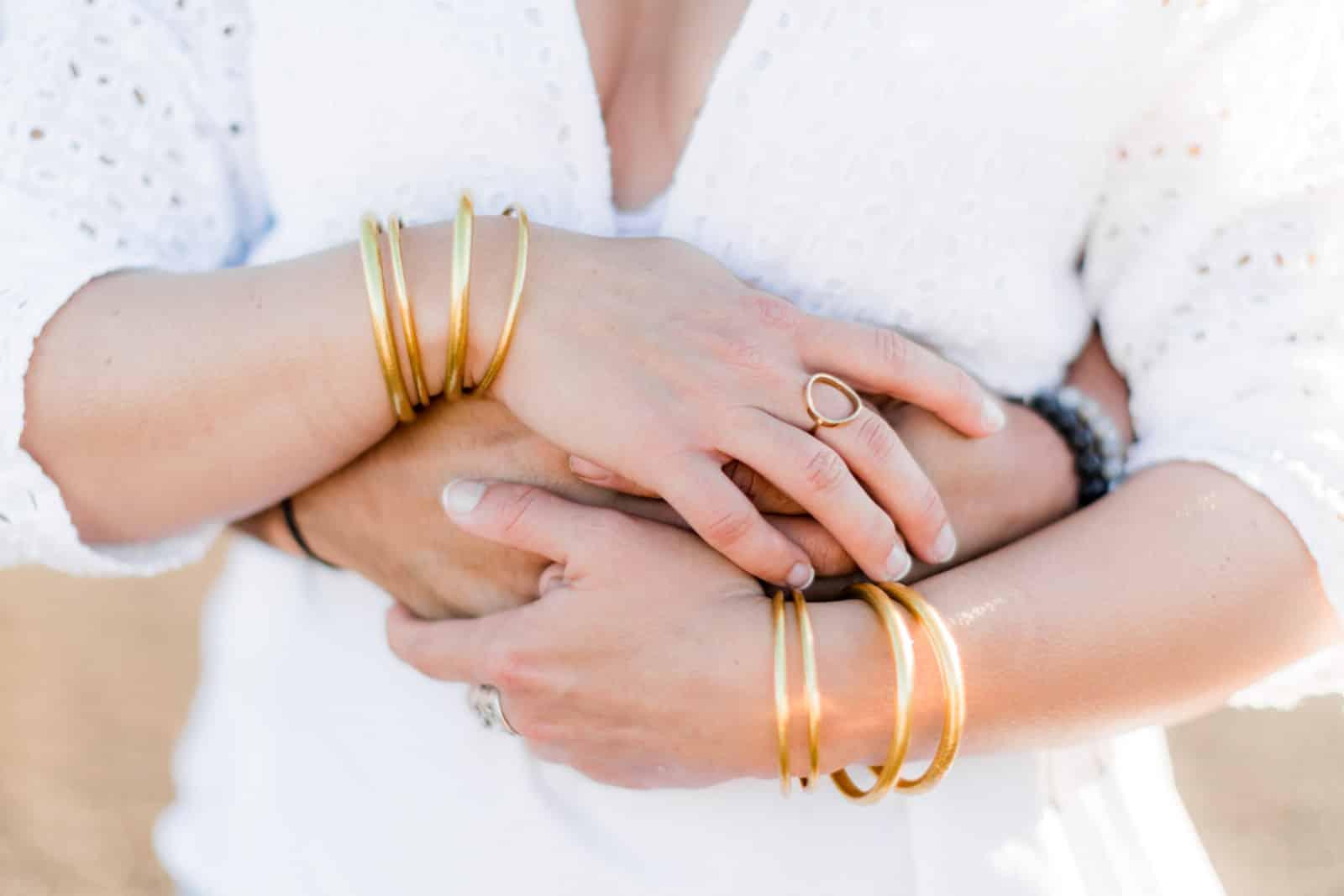 Photographie de Mathieu Dété, photographe de couple et famille à Saint-Leu sur l'île de la Réunion 974, présentant un le détail des mains et des bijoux d'un couple enlacé