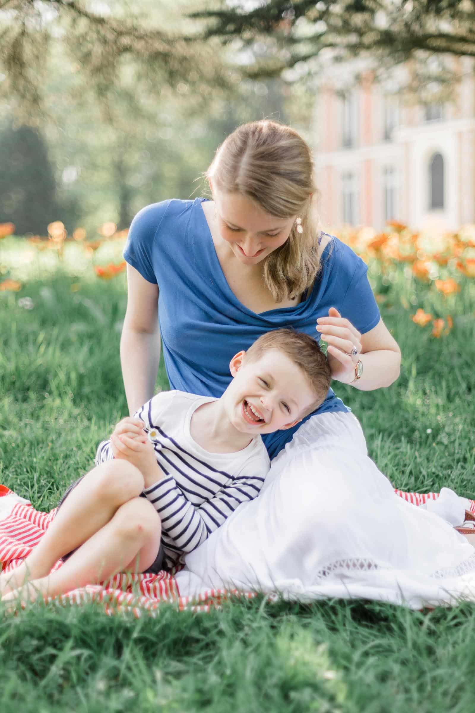 Photographie de Mathieu Dété, photographe de famille, présentant une maman jouant avec son enfant sur la pelouse
