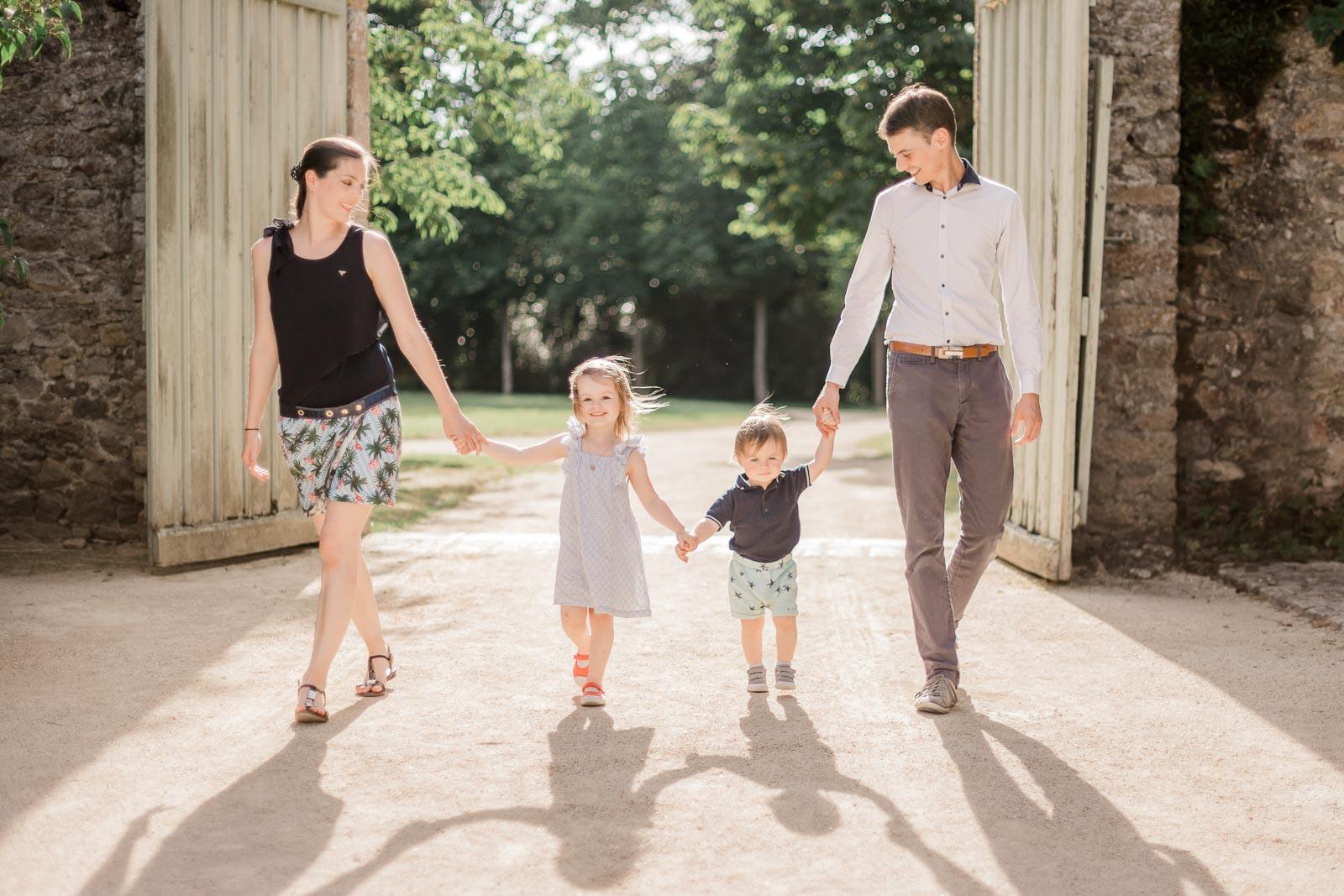 Photographie de Mathieu Dété, photographe de famille, présentant une famille de parents et leurs deux enfants se tenant par la main