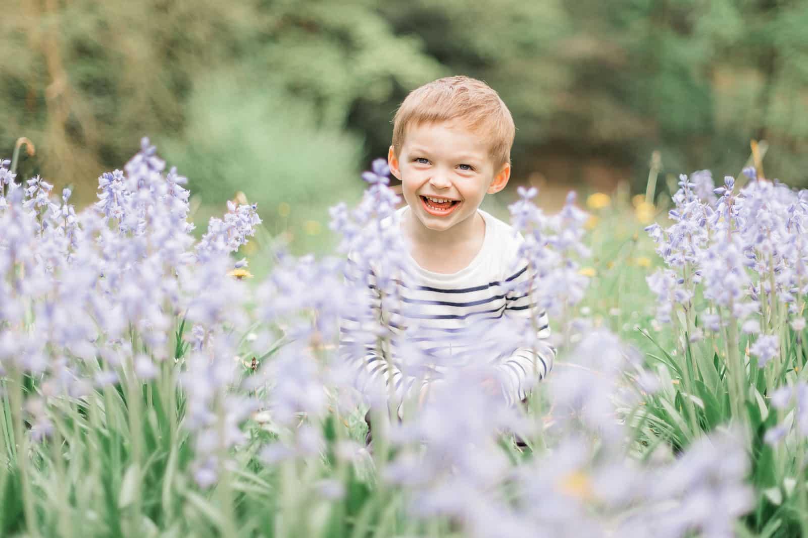 Photographie de Mathieu Dété, photographe de famille, présentant un enfant avec un grand sourire dans les fleurs