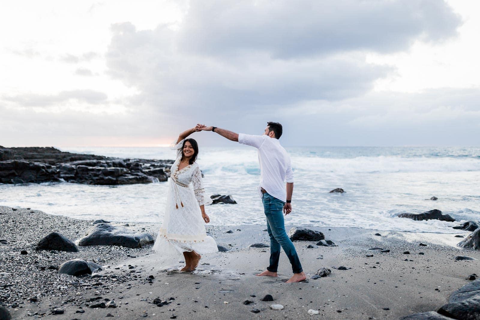 Photographie d'une séance photo au Cap La Houssaye, de Mathieu Dété, photographe de mariage et fiançailles à Saint-Pierre de la Réunion 974, présentant un couple qui danse en bord de mer au Cap la Houssaye