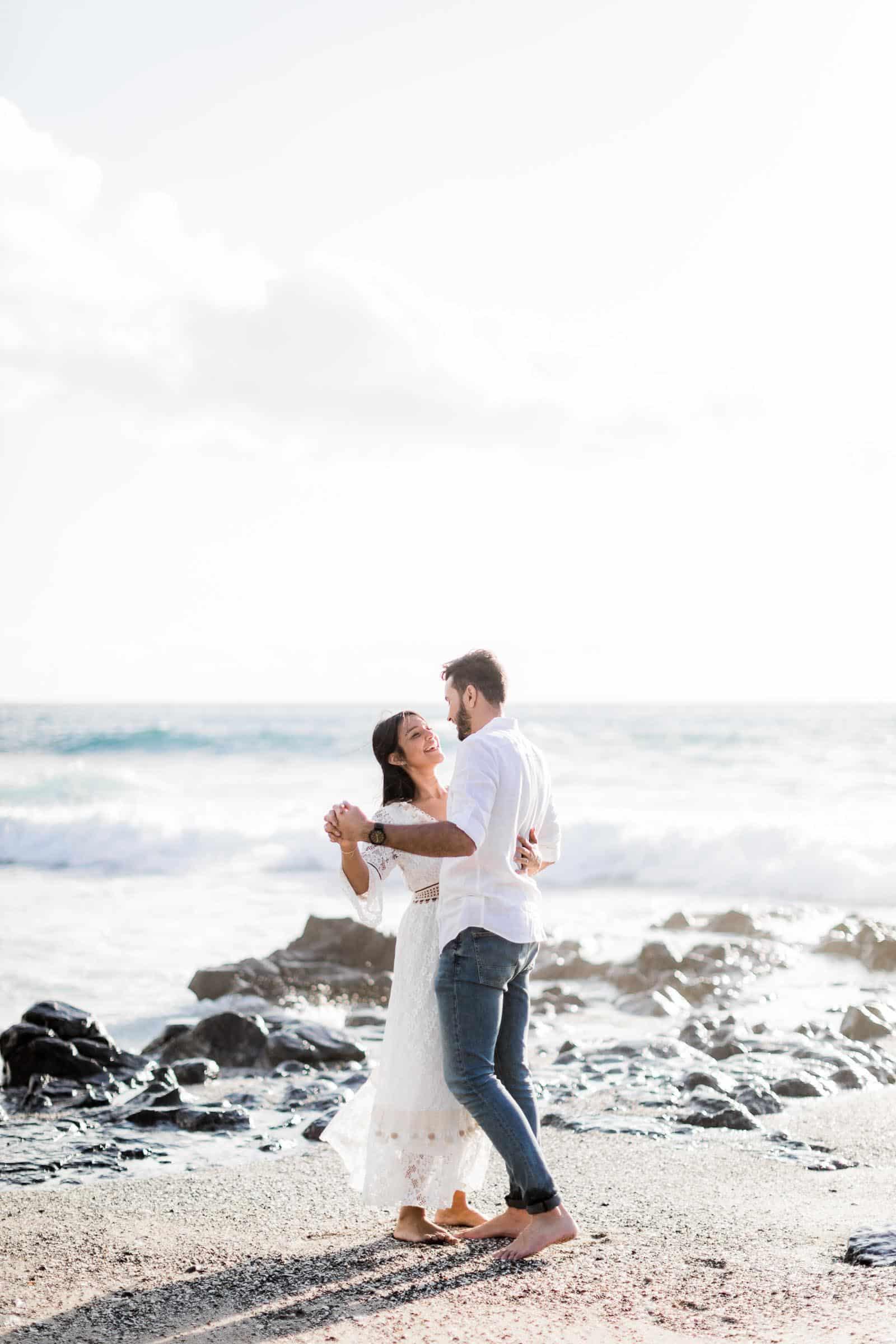 Photographie d'une séance photo au Cap La Houssaye, de Mathieu Dété, photographe de couple et famille à Saint-Denis de la Réunion 974, présentant un couple qui danse les pieds dans l'eau de l'Océan Indien