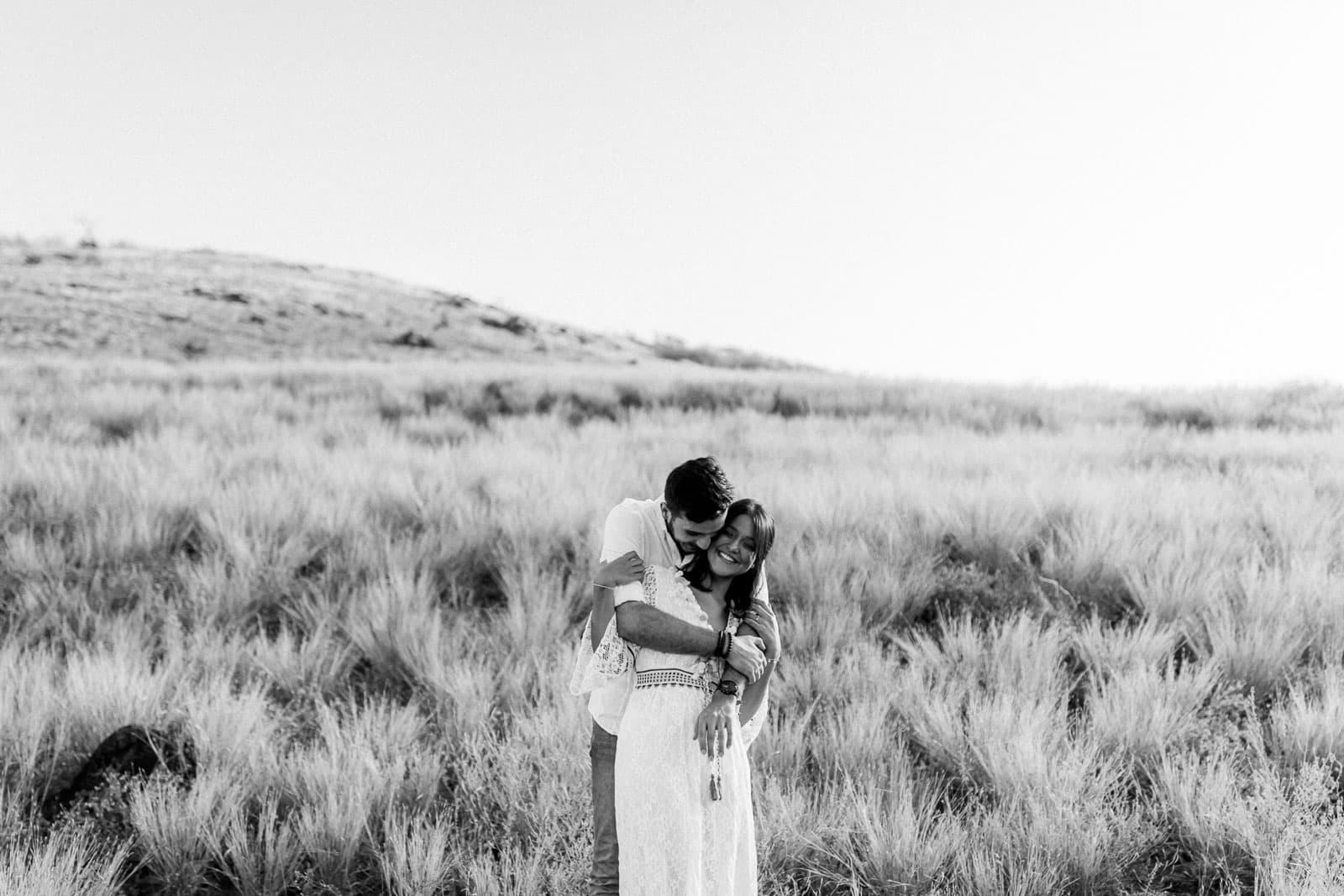 Photo d'une séance photo au Cap La Houssaye, de Mathieu Dété, en noir et blanc, photographe de mariage et famille à Saint-Gilles de la Réunion 974, présentant un couple enlacé dans la savane du Cap La Houssaye, près de Saint-Paul