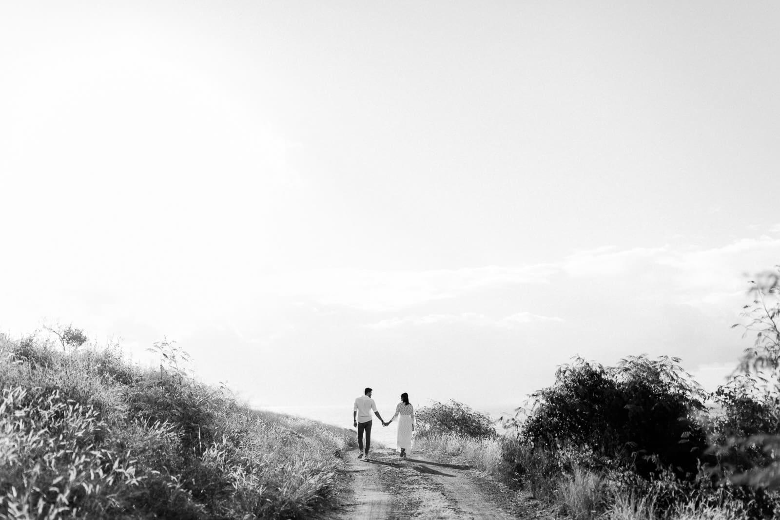 Photographie de Mathieu Dété en noir et blanc, photographe de mariage et famille à Saint-Gilles de la Réunion 974, présentant un couple qui marche dans la savane du Cap La Houssaye, près de Saint-Paul