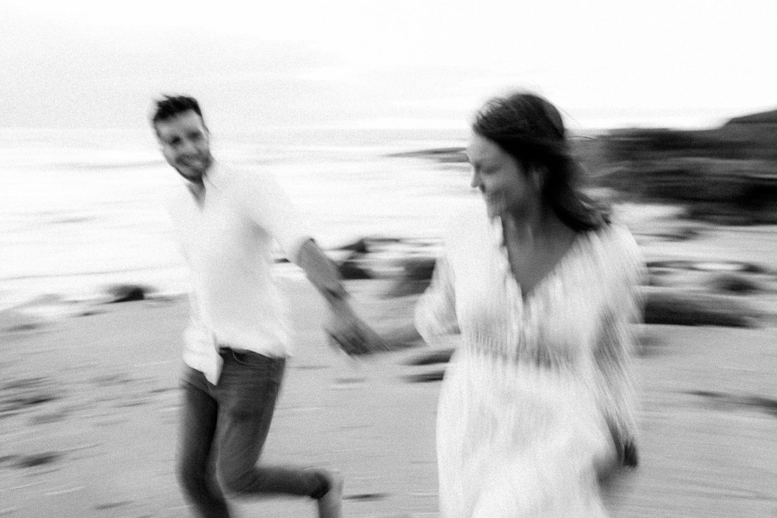 Photographie de Mathieu Dété, photographe de mariage et fiançailles à Saint-Pierre de la Réunion 974, présentant un couple qui court en bord de mer, en noir et blanc