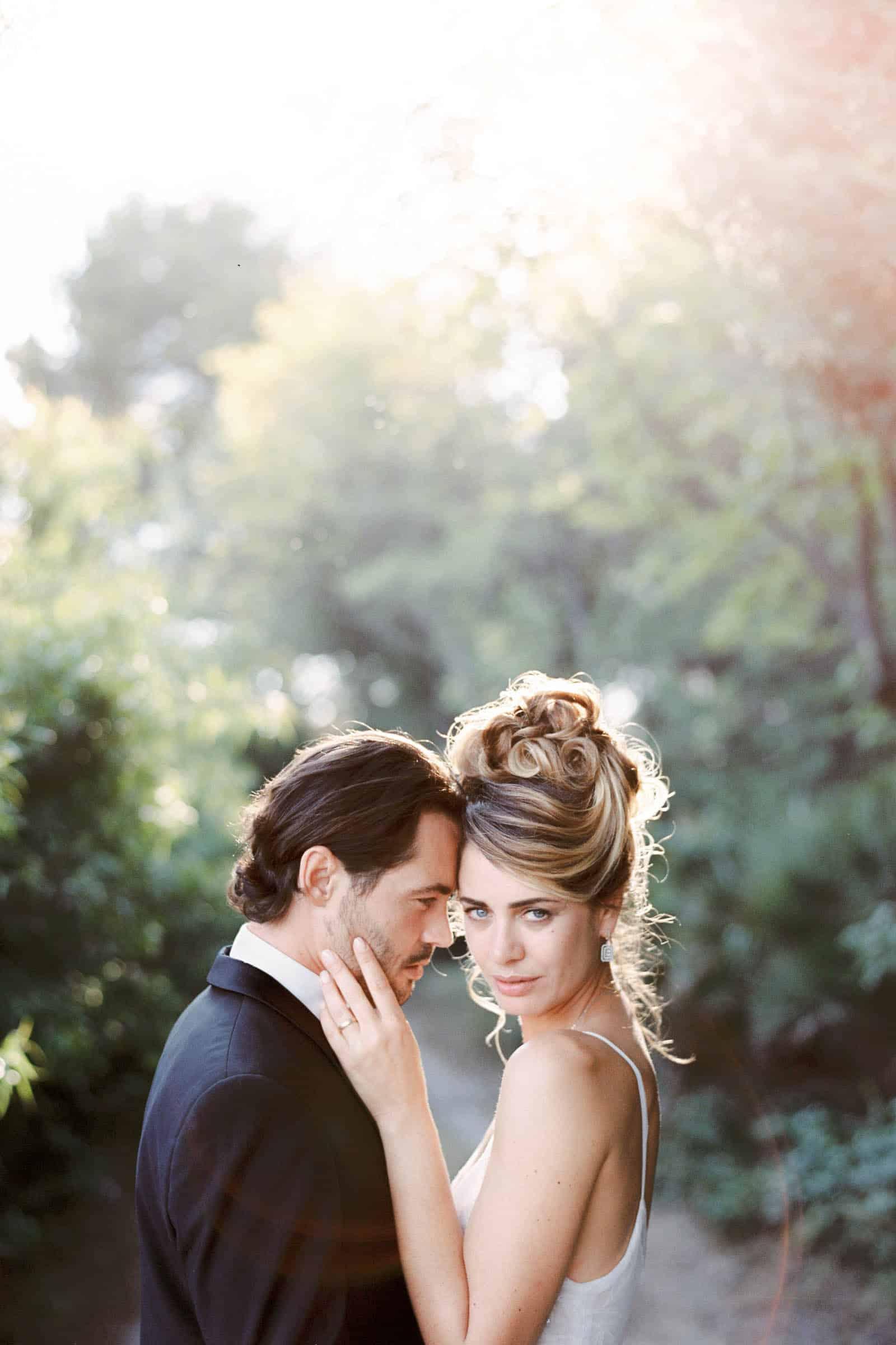 Photographie de Mathieu Dété présentant un portrait de mariés dans une allée d'oliviers au soleil couchant