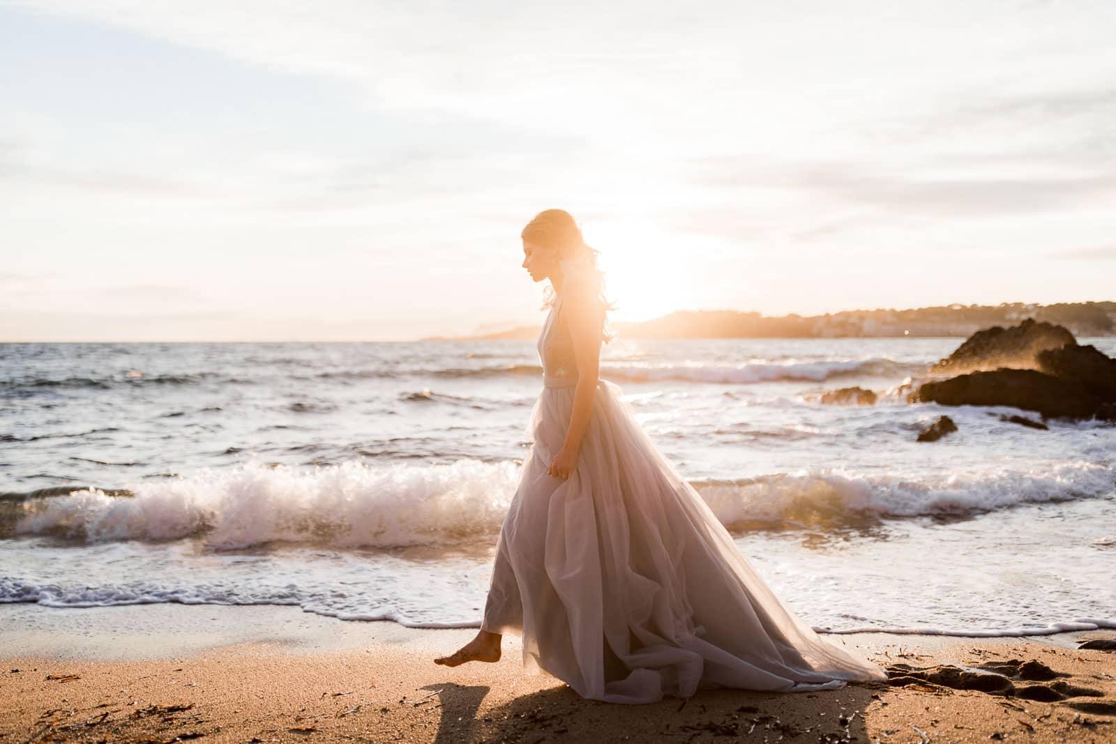 Photographie de Mathieu Dété, photographe de mariage et couple à Saint-Denis de la Réunion (974), présentant un portrait de la mariée qui marche sur la plage au coucher de soleil en bord de mer