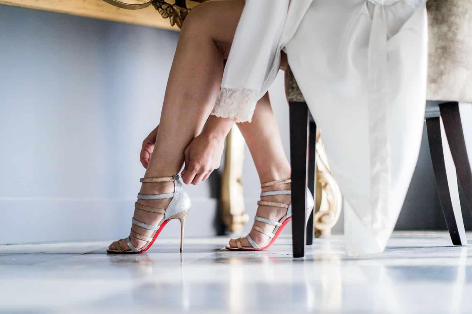 Photographie de Mathieu Dété présentant l'habillage des chaussures de la mariée à la Villa Brignac