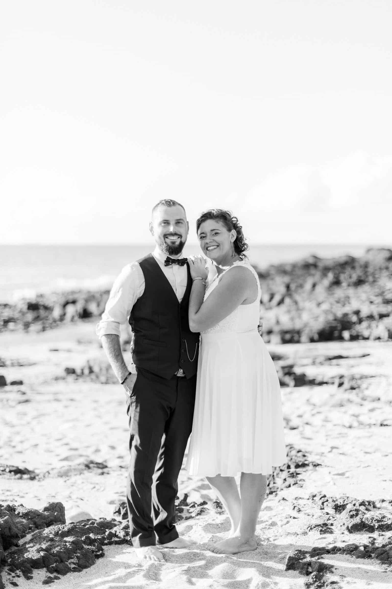 Photo de Mathieu Dété lors d'un mariage sur l'île de la Réunion 974, au Cap La Houssaye, avec un portrait des mariés en noir et blanc les pieds dans le sable de l'Océan Indien