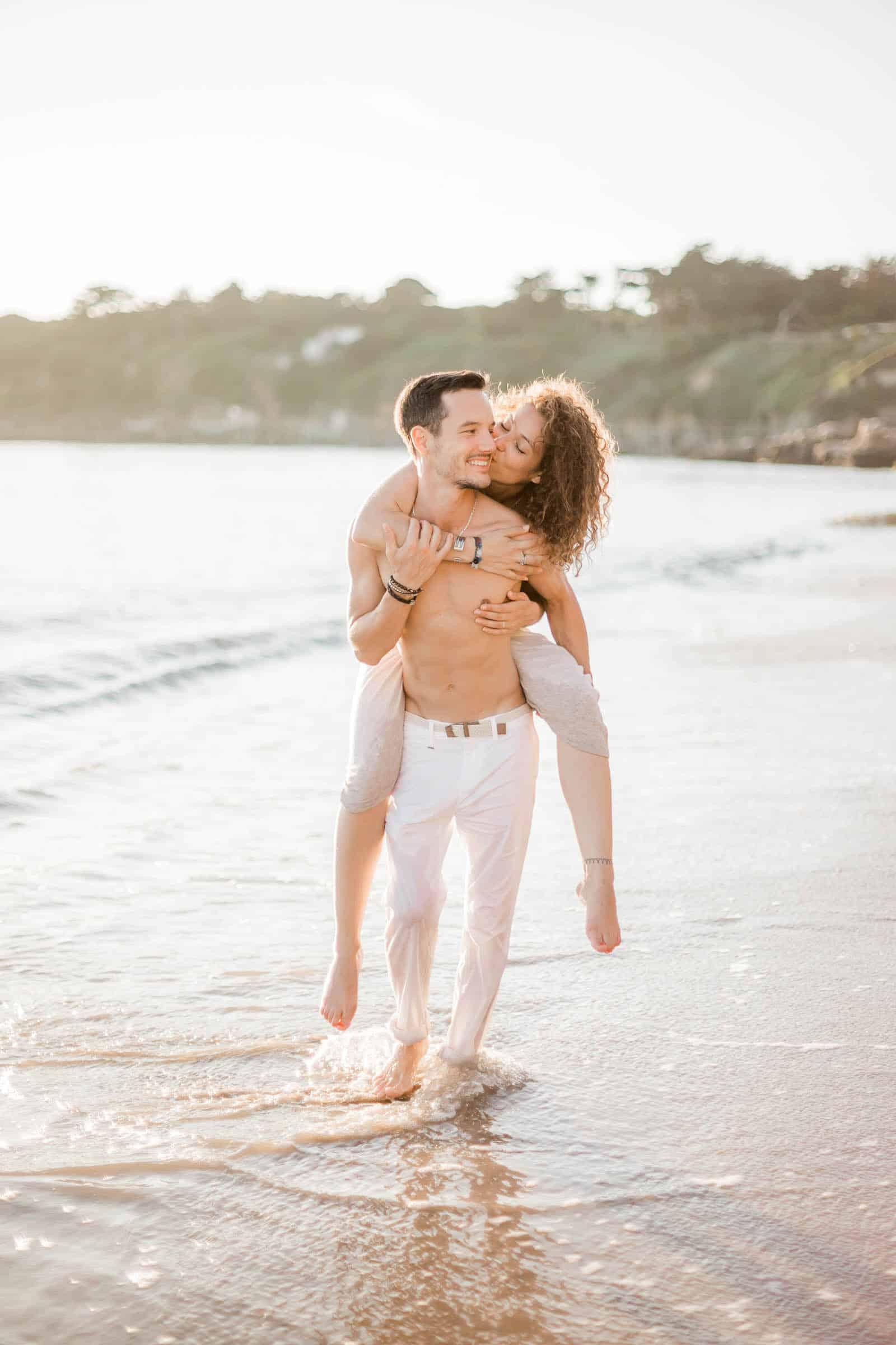 Photographie de Mathieu Dété, photographe couple la Réunion, présentant un couple heureux marchant en bord de mer et en train de rigoler sur la plage de Saint Paul
