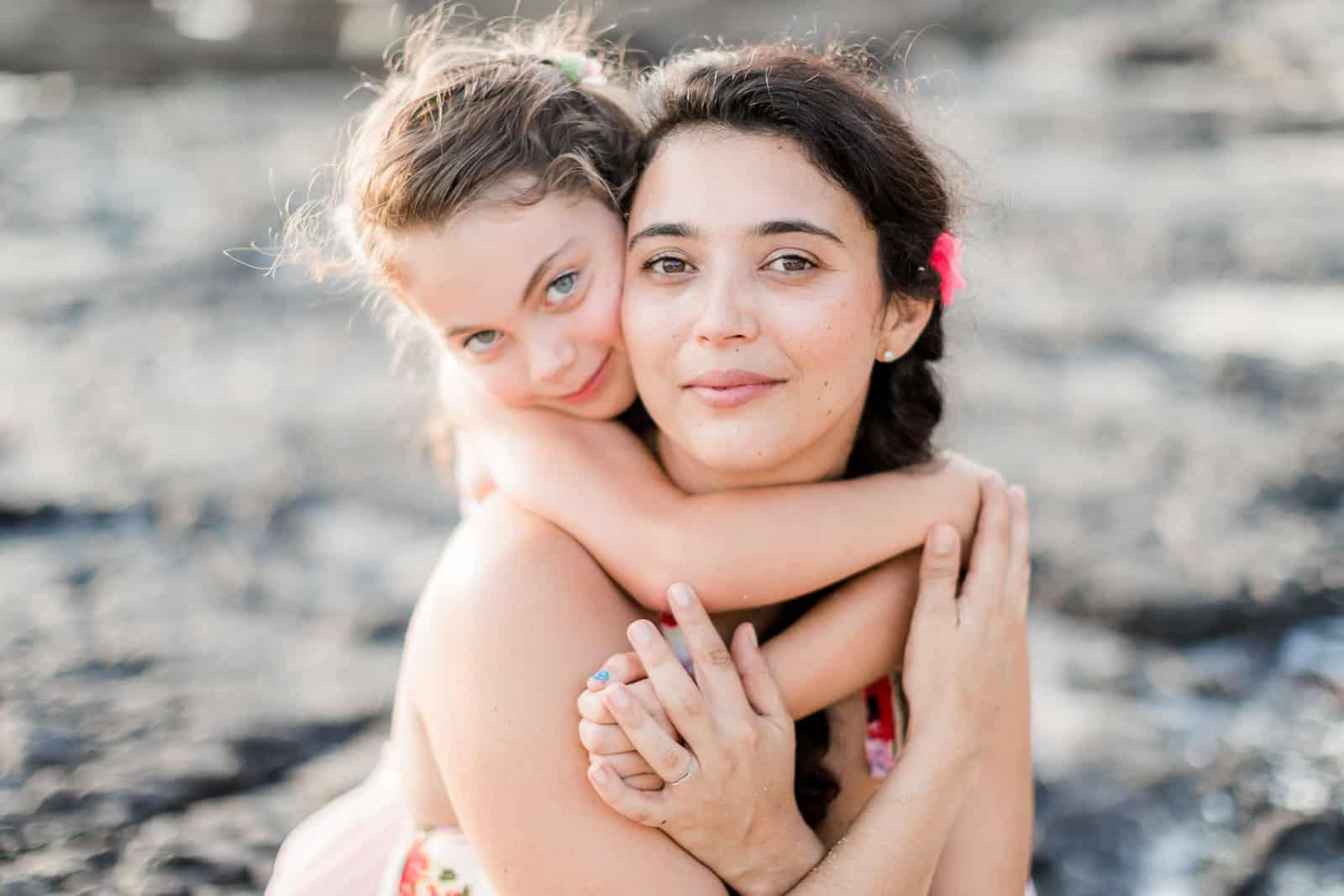 Photographie de Mathieu Dété, photographe de mariage et famille à Saint-Gilles sur l'île de la Réunion 974, présentant une étreinte en famille avec une enfant au Cap La Houssaye
