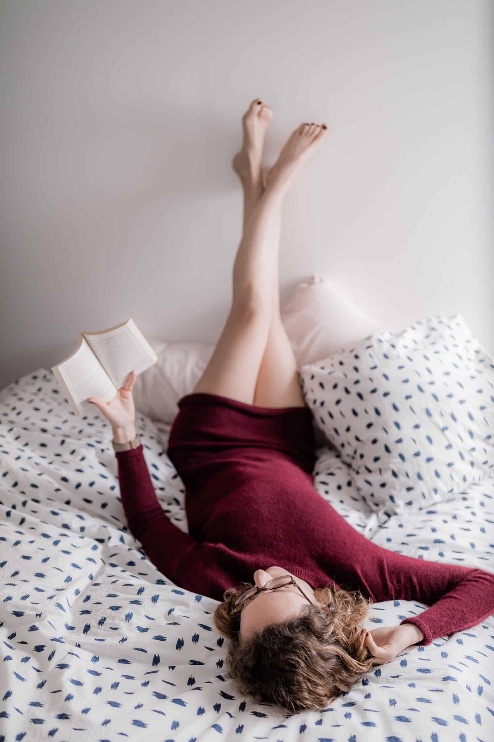 Femme couchée qui lit sur le lit